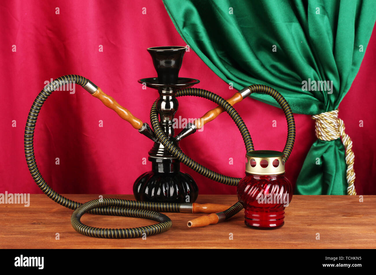 hookah on a wooden table on a background of curtain close-up - Stock Image