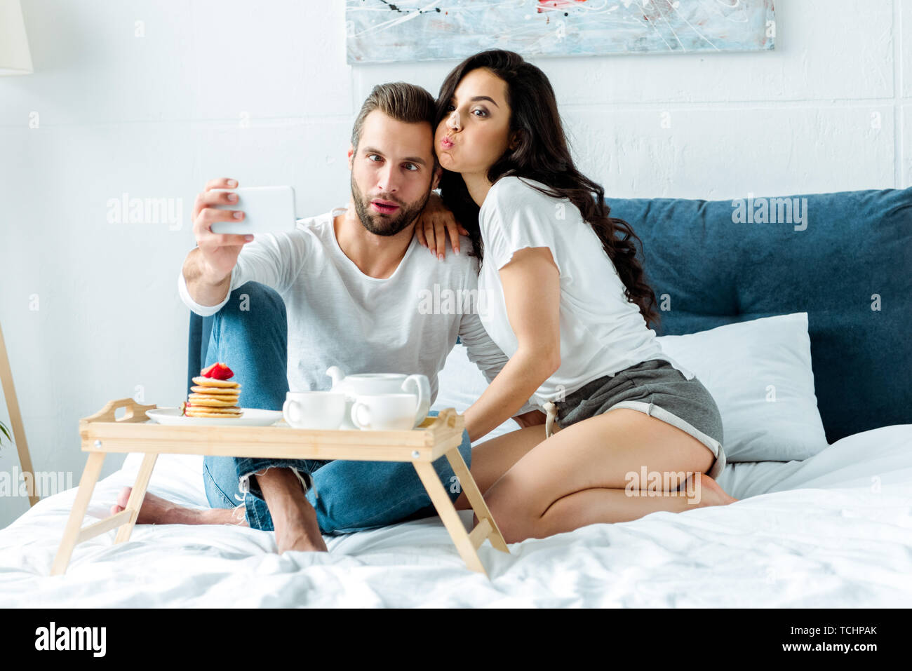 funny couple grimacing taking selfie on smartphone near wooden tray with breakfast in bed - Stock Image