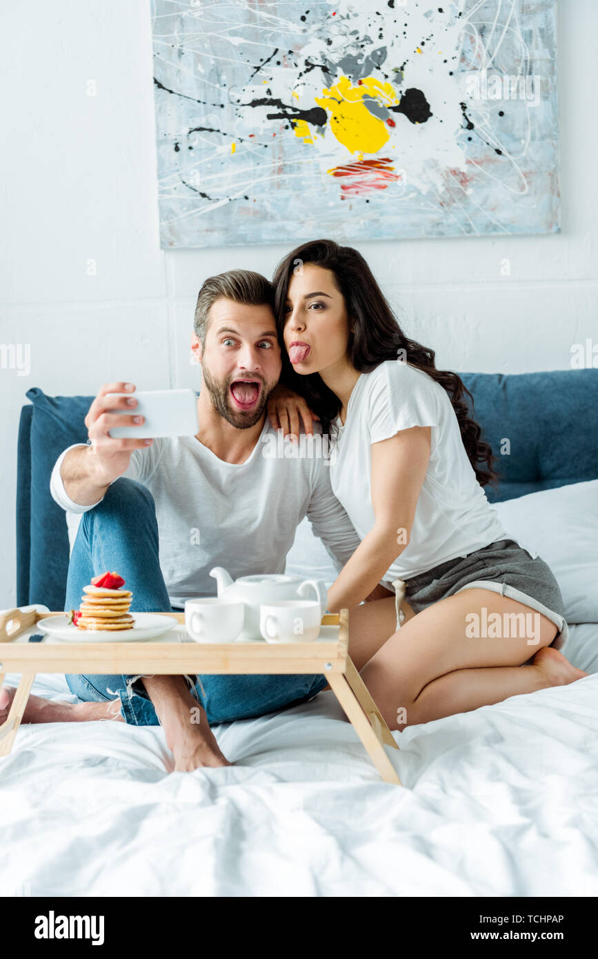 happy couple grimacing while taking selfie on smartphone near wooden tray with breakfast in bed - Stock Image