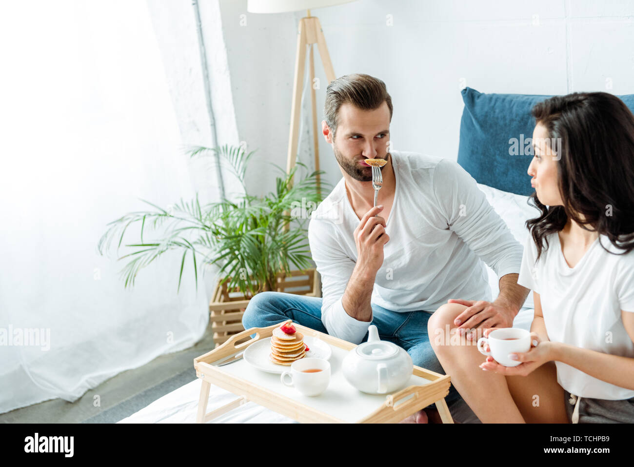 funny couple grimacing near wooden tray with breakfast in bed - Stock Image