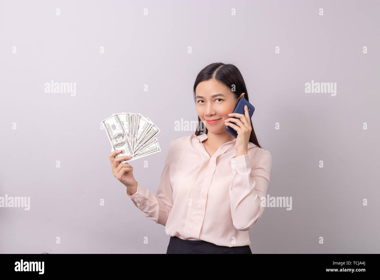 Asian beautiful woman holding banknote money in hand and mobile phone in another hand isolated on grey background. commercial business by phone concep Stock Photo