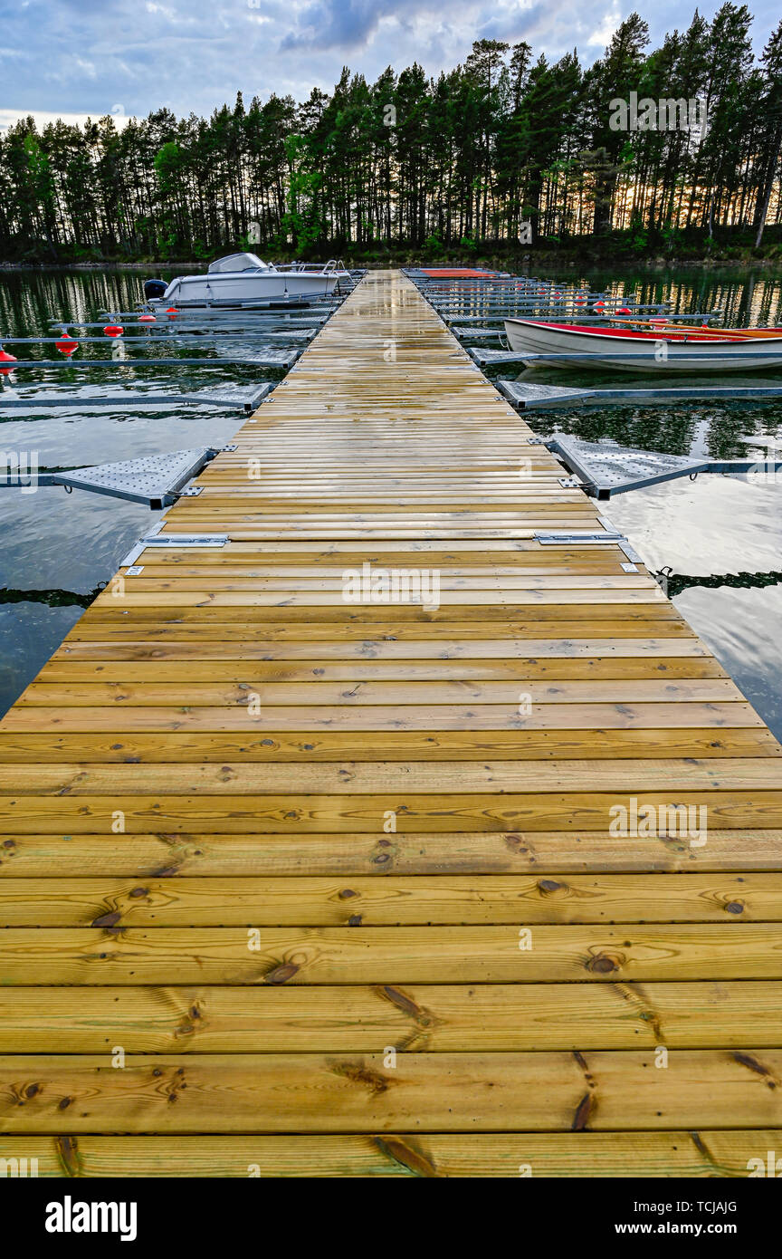 wooden jetty with just a few boats in Motala Sweden - Stock Image