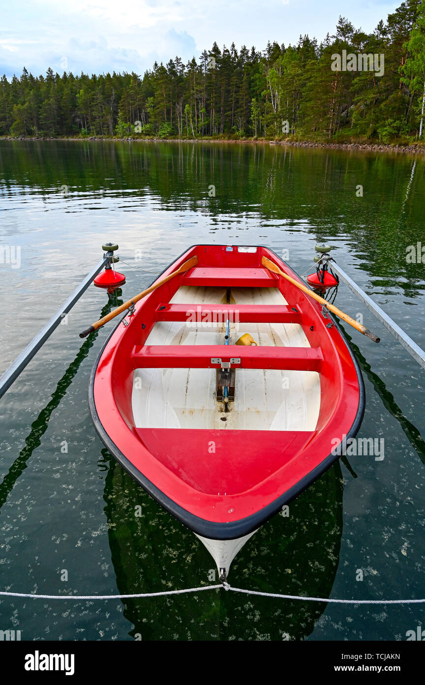 little red and white skiff in Swedish lake may 2019 - Stock Image