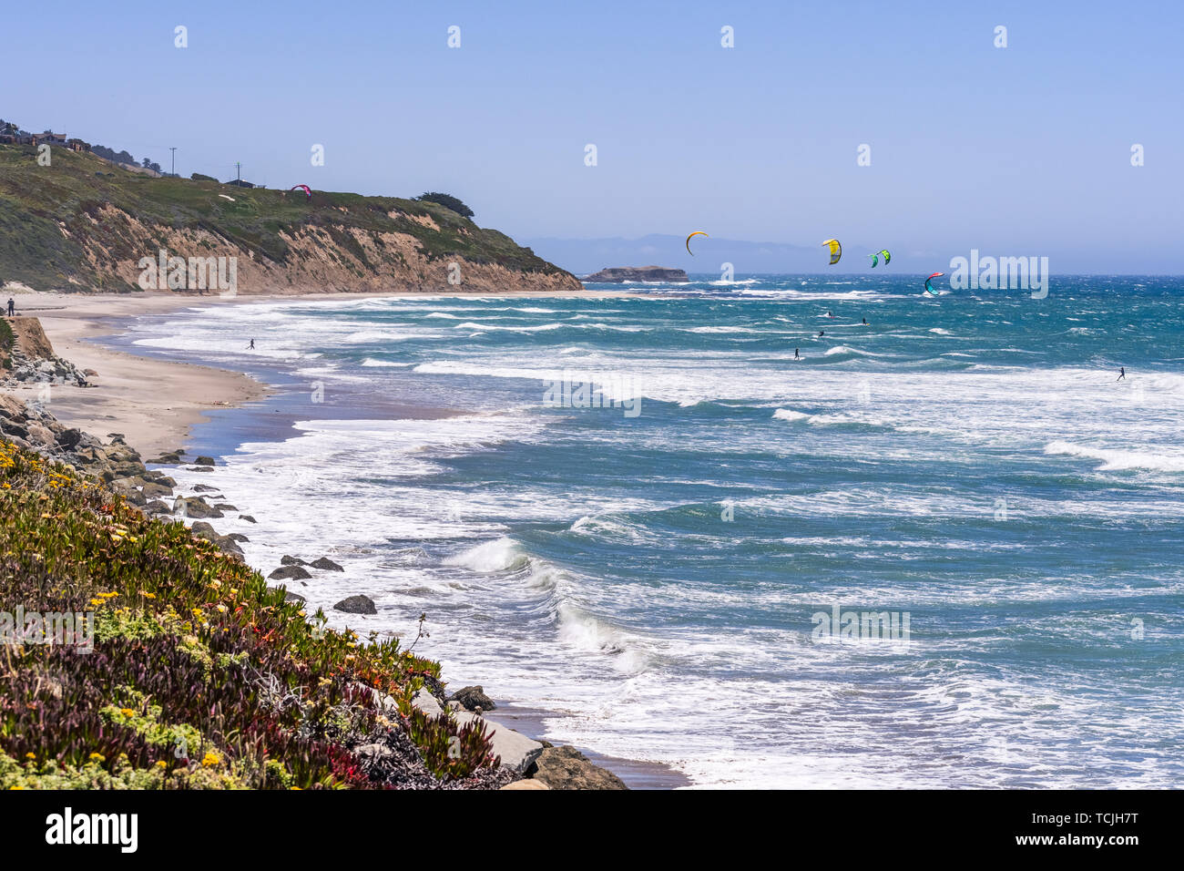 The Pacific Ocean coastline close to Santa Cruz, California; unidentified people windsurfing on a sunny day at Waddell Beach - Stock Image