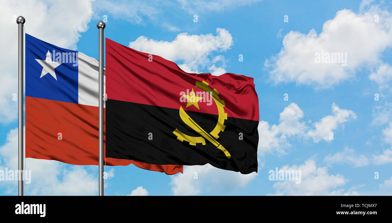 Chile and Angola flag waving in the wind against white cloudy blue sky together. Diplomacy concept, international relations. - Stock Image