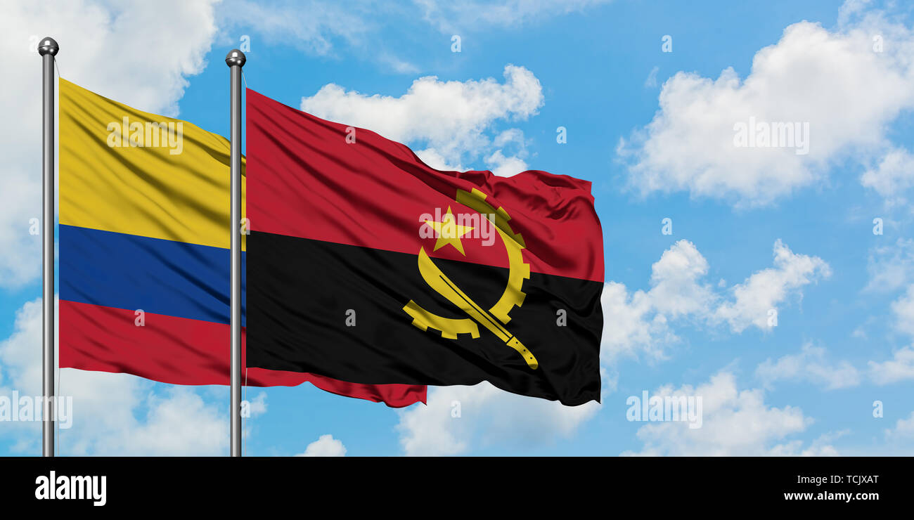 Colombia and Angola flag waving in the wind against white cloudy blue sky together. Diplomacy concept, international relations. - Stock Image