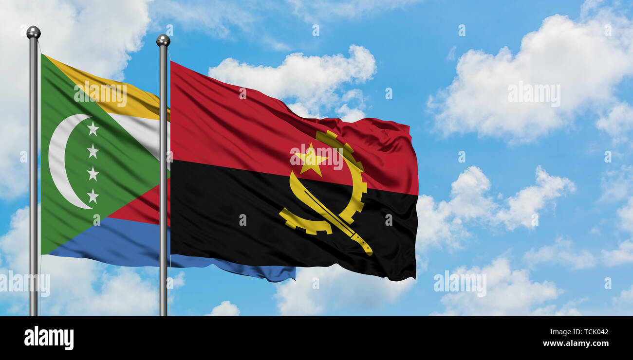 Comoros and Angola flag waving in the wind against white cloudy blue sky together. Diplomacy concept, international relations. Stock Photo