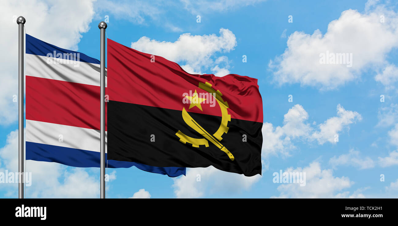 Costa Rica and Angola flag waving in the wind against white cloudy blue sky together. Diplomacy concept, international relations. - Stock Image