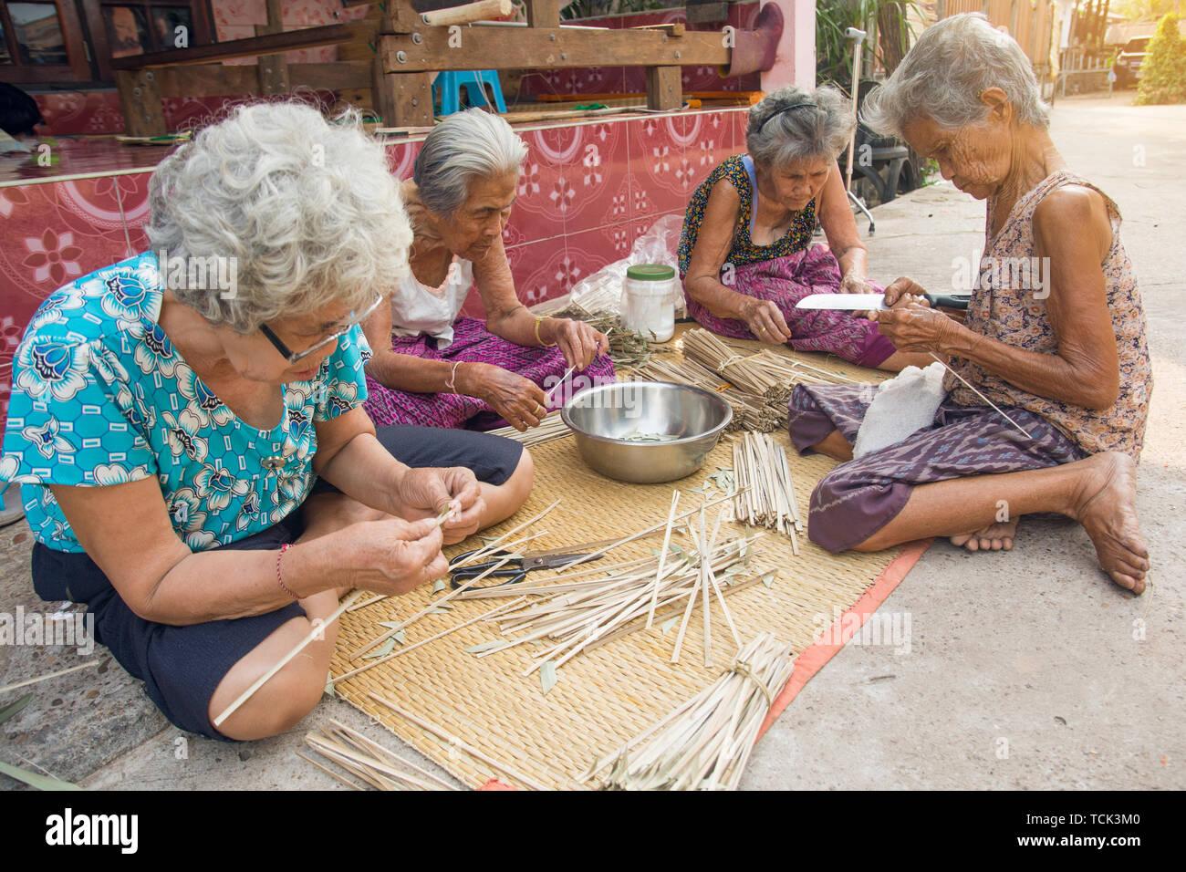 NAKHON PHANOM, THAILAND - Mar 25, 2019 : Group Senior Woman manually weaving bamboo. - Stock Image