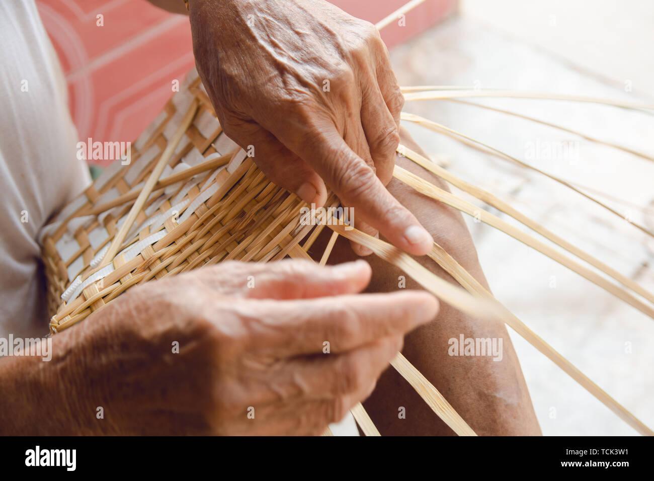Senior man hands manually weaving bamboo. - Stock Image