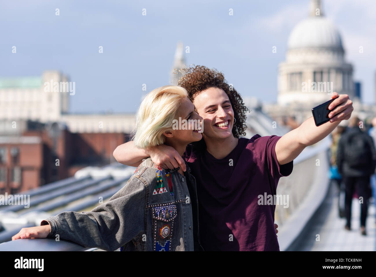 Happy couple taking a selfie photograph on London's Millennium Bridge - Stock Image