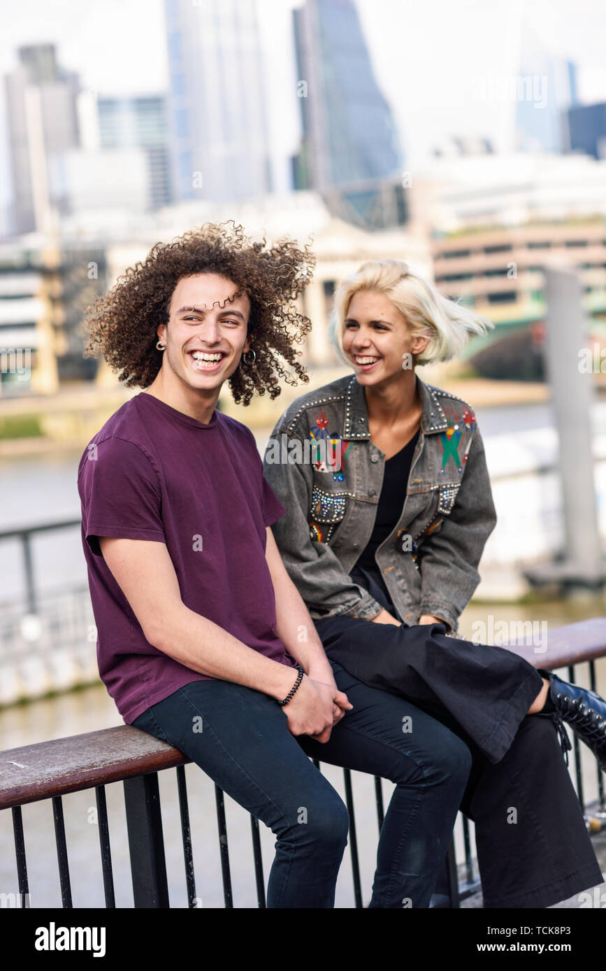 Happy couple talking sitting near River Thames. - Stock Image