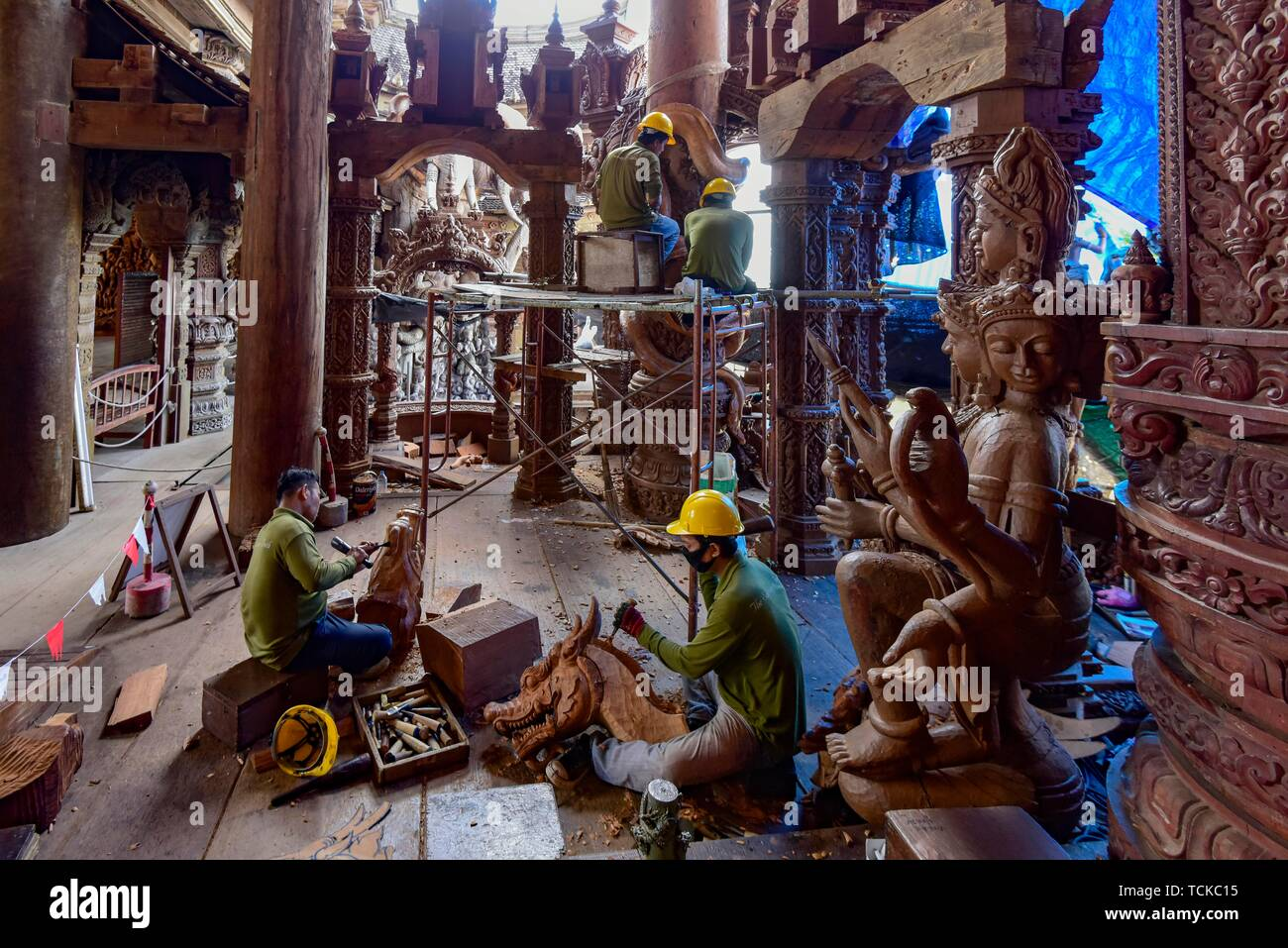 Craftsman carving wooden figures in the Sanctuary of Truth Temple, Pattaya, Thailand - Stock Image