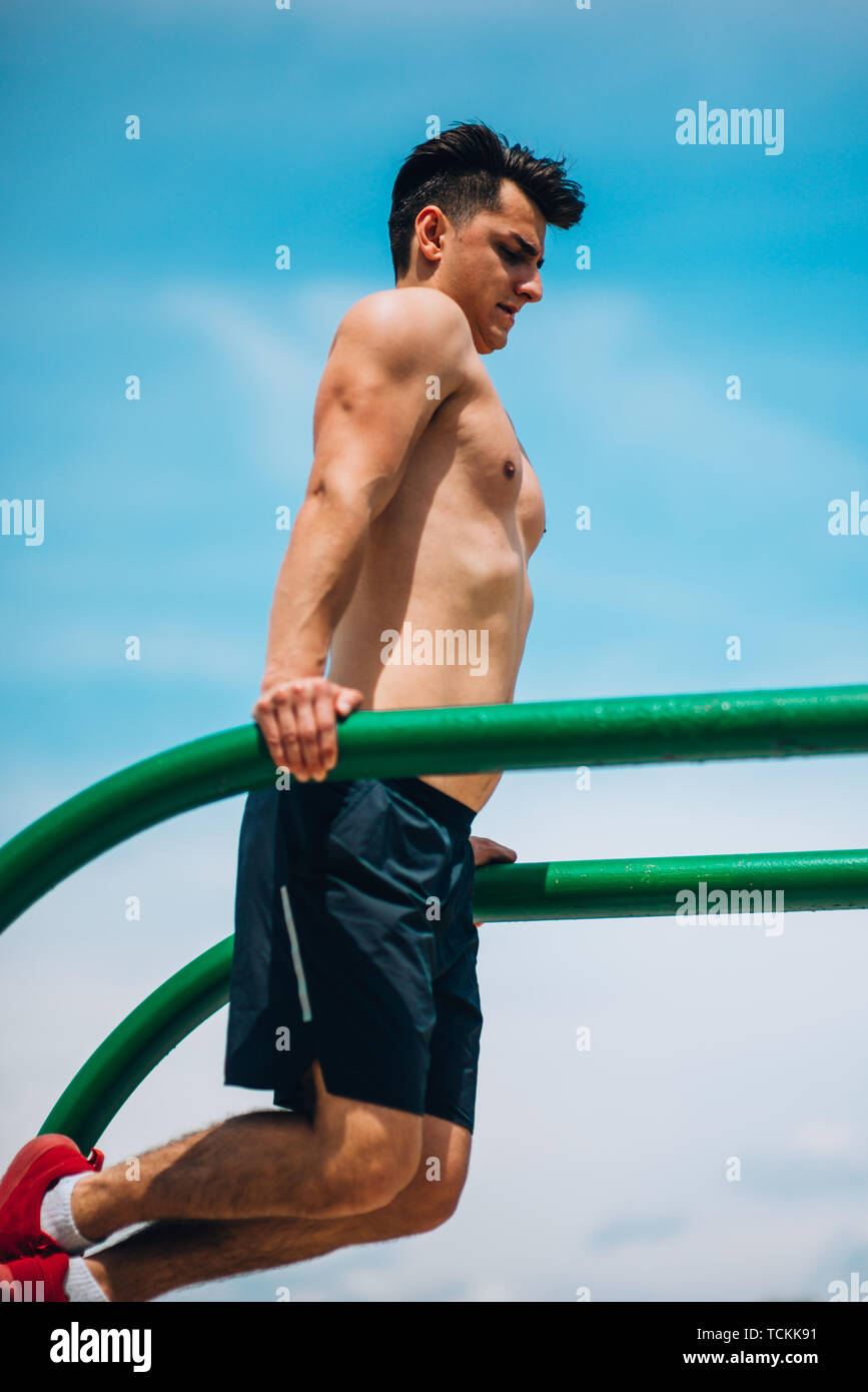 Strong and physically fit young man doing triceps dips on parallel bars at park - Stock Image