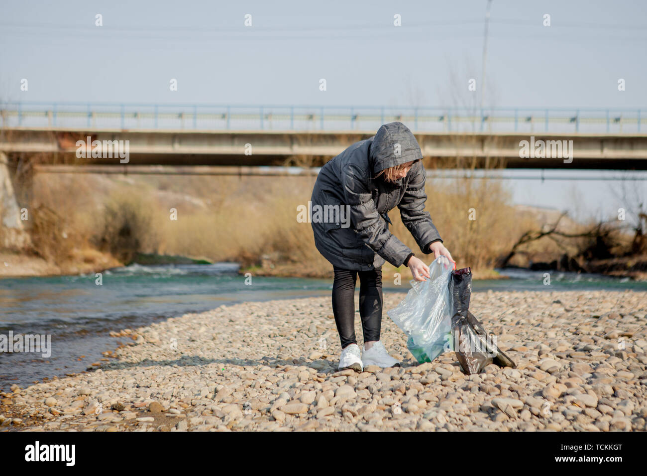Young woman collecting plastic trash from the beach and putting it into black plastic bags for recycle. Cleaning and recycling concept - Stock Image