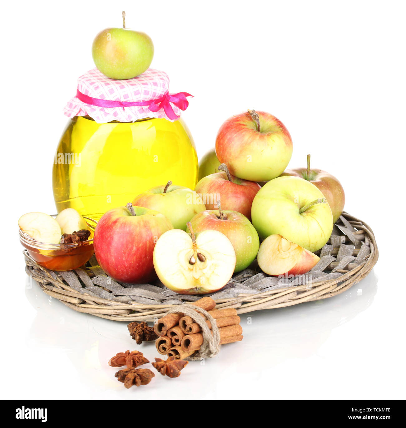 Honey and apples with cinnamon on wicker cradle isolated on white - Stock Image