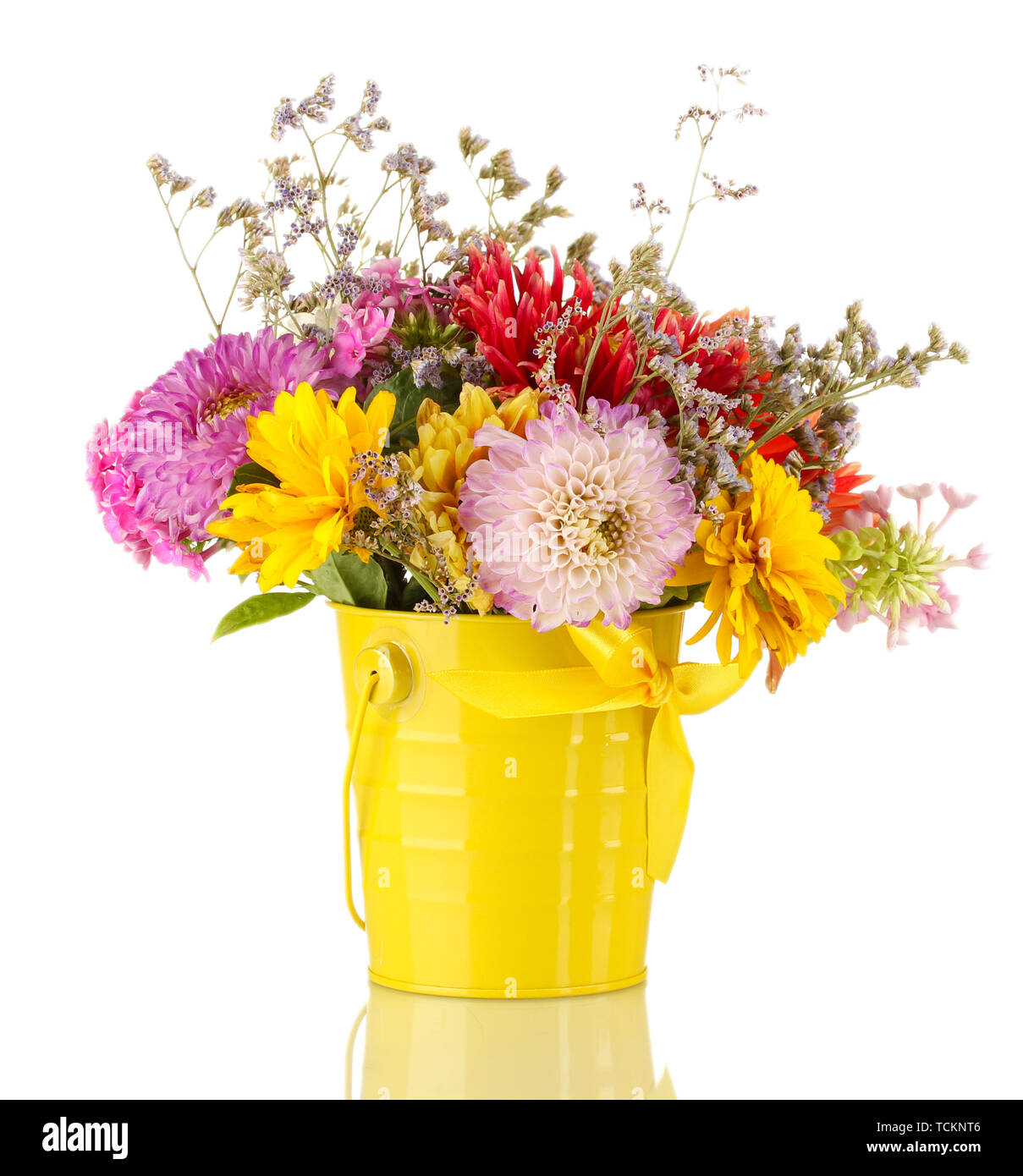 Bright yellow bucket with flowers isolated on white - Stock Image