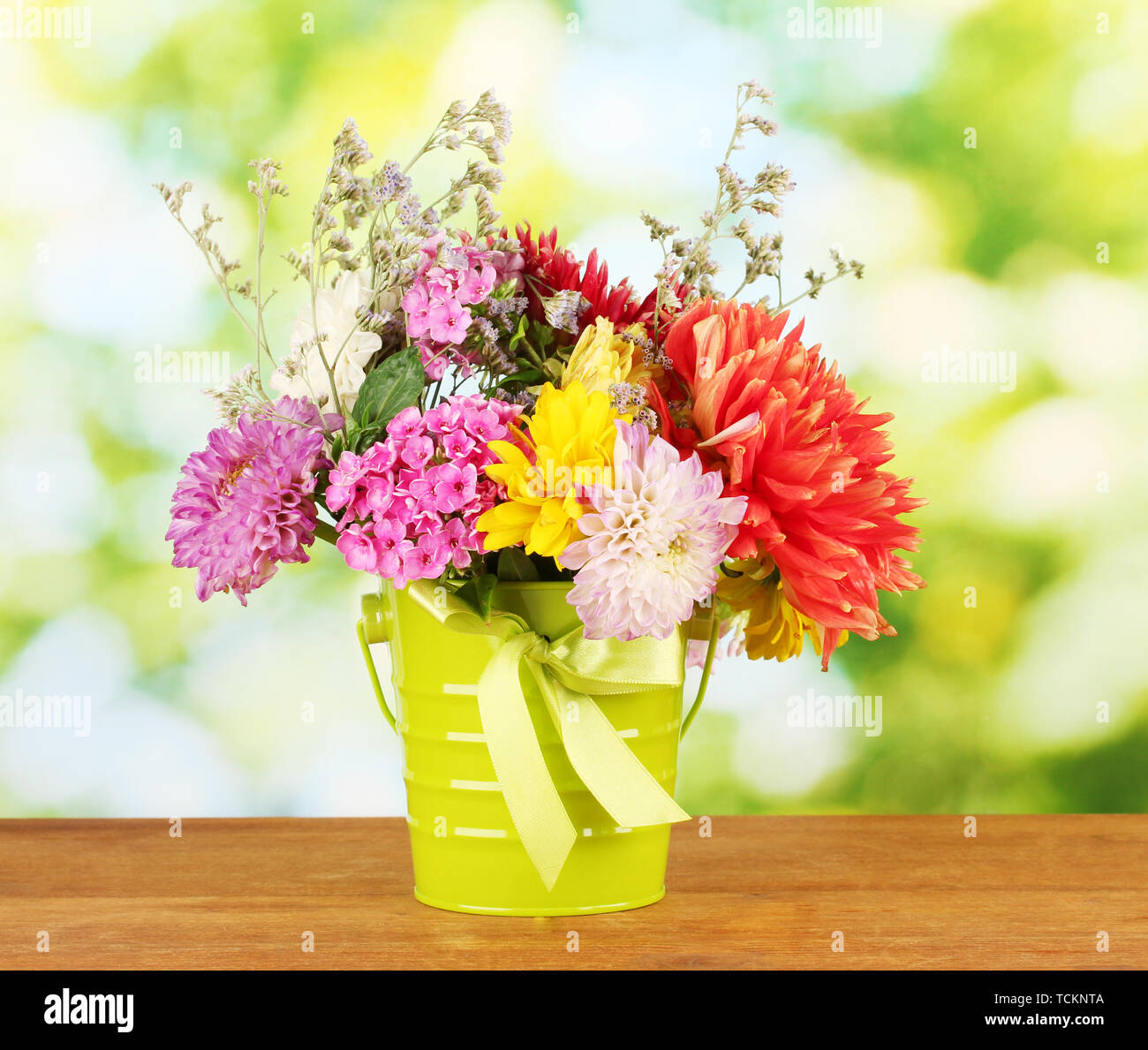 Bright green bucket with flowers on green background - Stock Image