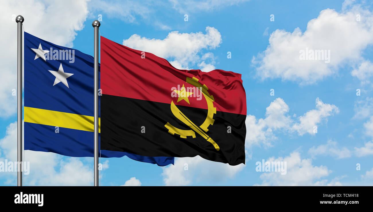 Curacao and Angola flag waving in the wind against white cloudy blue sky together. Diplomacy concept, international relations. - Stock Image