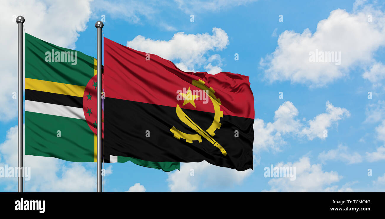 Dominica and Angola flag waving in the wind against white cloudy blue sky together. Diplomacy concept, international relations. - Stock Image