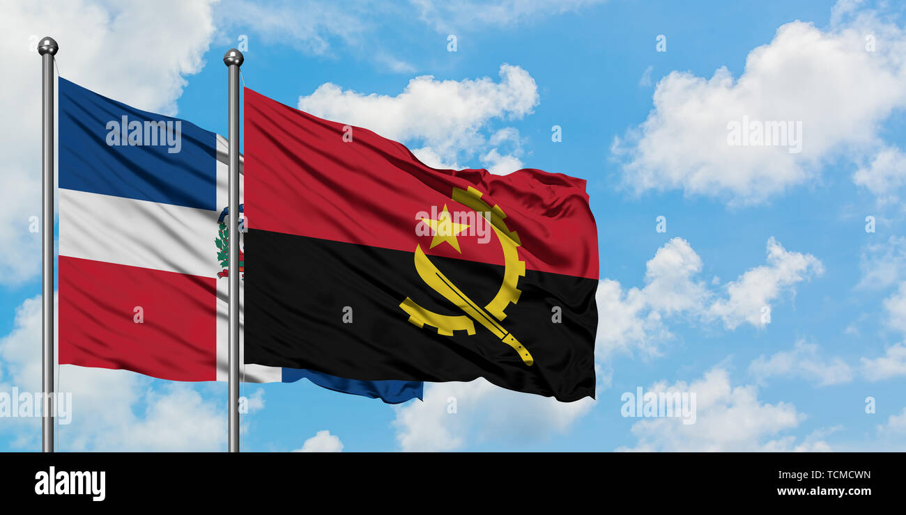 Dominican Republic and Angola flag waving in the wind against white cloudy blue sky together. Diplomacy concept, international relations. - Stock Image