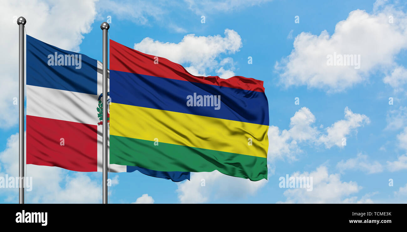 Dominican Republic and Mauritius flag waving in the wind against white cloudy blue sky together. Diplomacy concept, international relations. - Stock Image