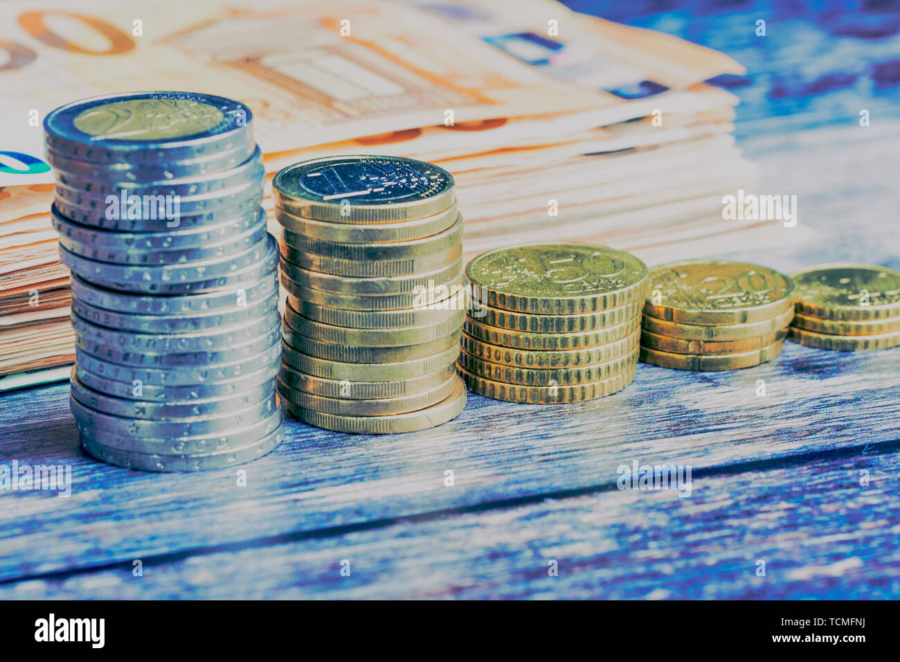 stacks of Euro coins and cent coins in front of blurred banknotes on a wooden background in a cold color style - Stock Image