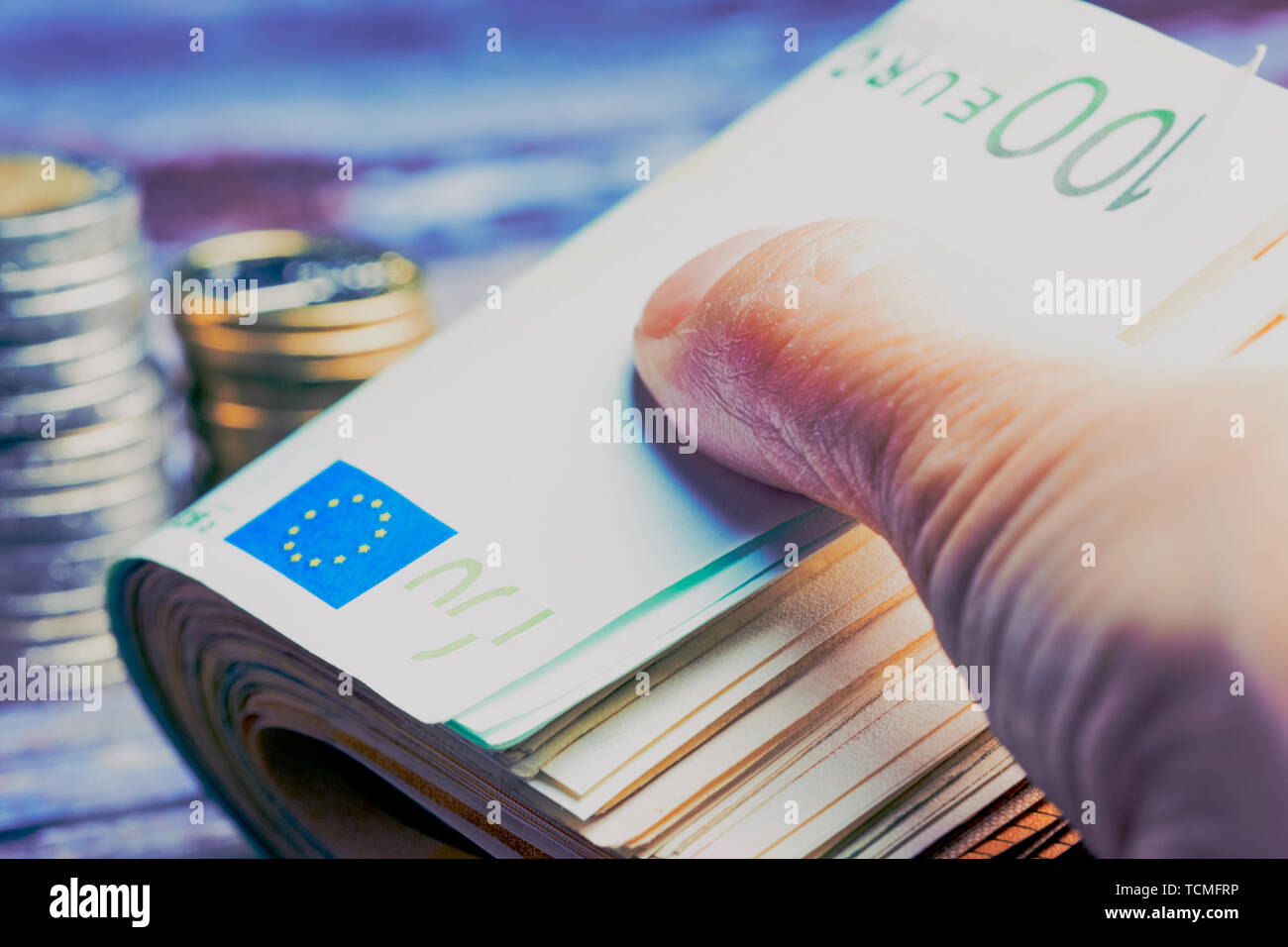 female hand close up whilst holding bunch of Euro banknotes with one hundred note, in the background lying blurred Euro coins, cold color style - Stock Image