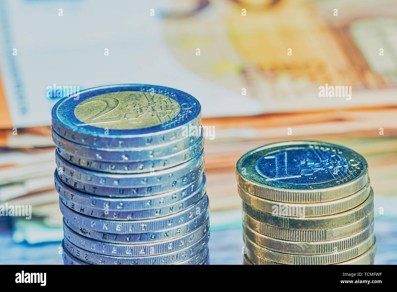 stack with one Euro coins beside a stack of two Euro coins, in the background lying blurred Euro banknotes, cold color style - Stock Image