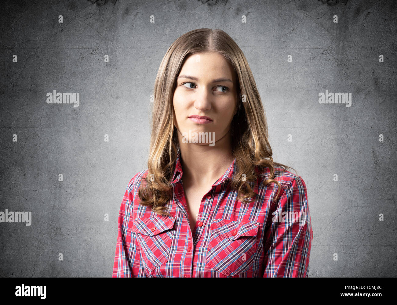 Distrustful brown haired woman looks suspiciously - Stock Image