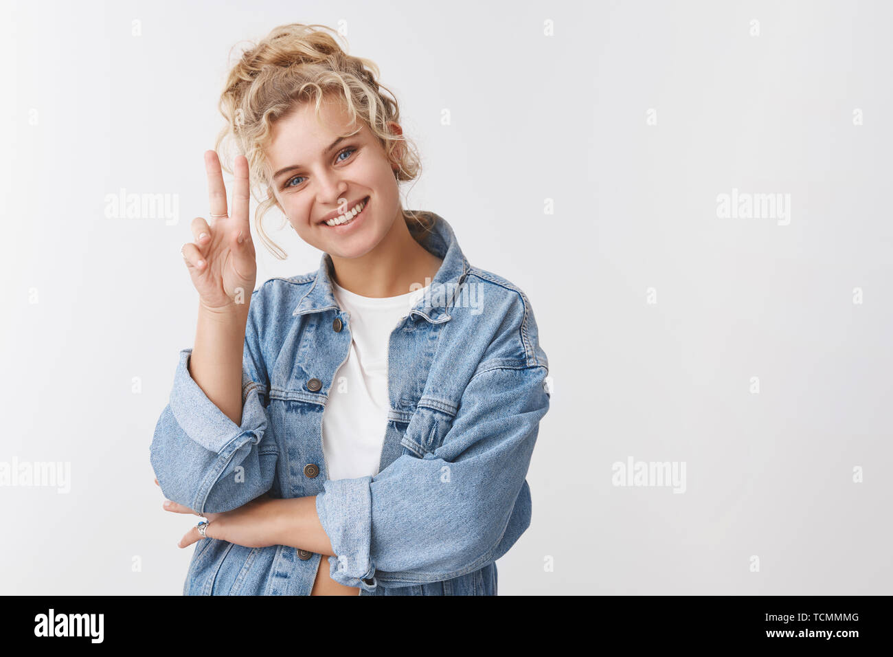 Joyful optimistic attractive blond european girl curly bun haircut show victory peace gesture staying cool having fun smiling broadly expressing happi - Stock Image