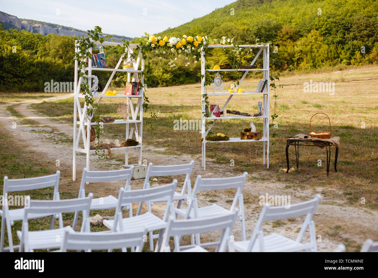 Happy Outdoor Ceremony Scene For A Summer Mountain Wedding. Wed Aisle,  Decorated Alter And Flower Decorations With Mountains In The Background.