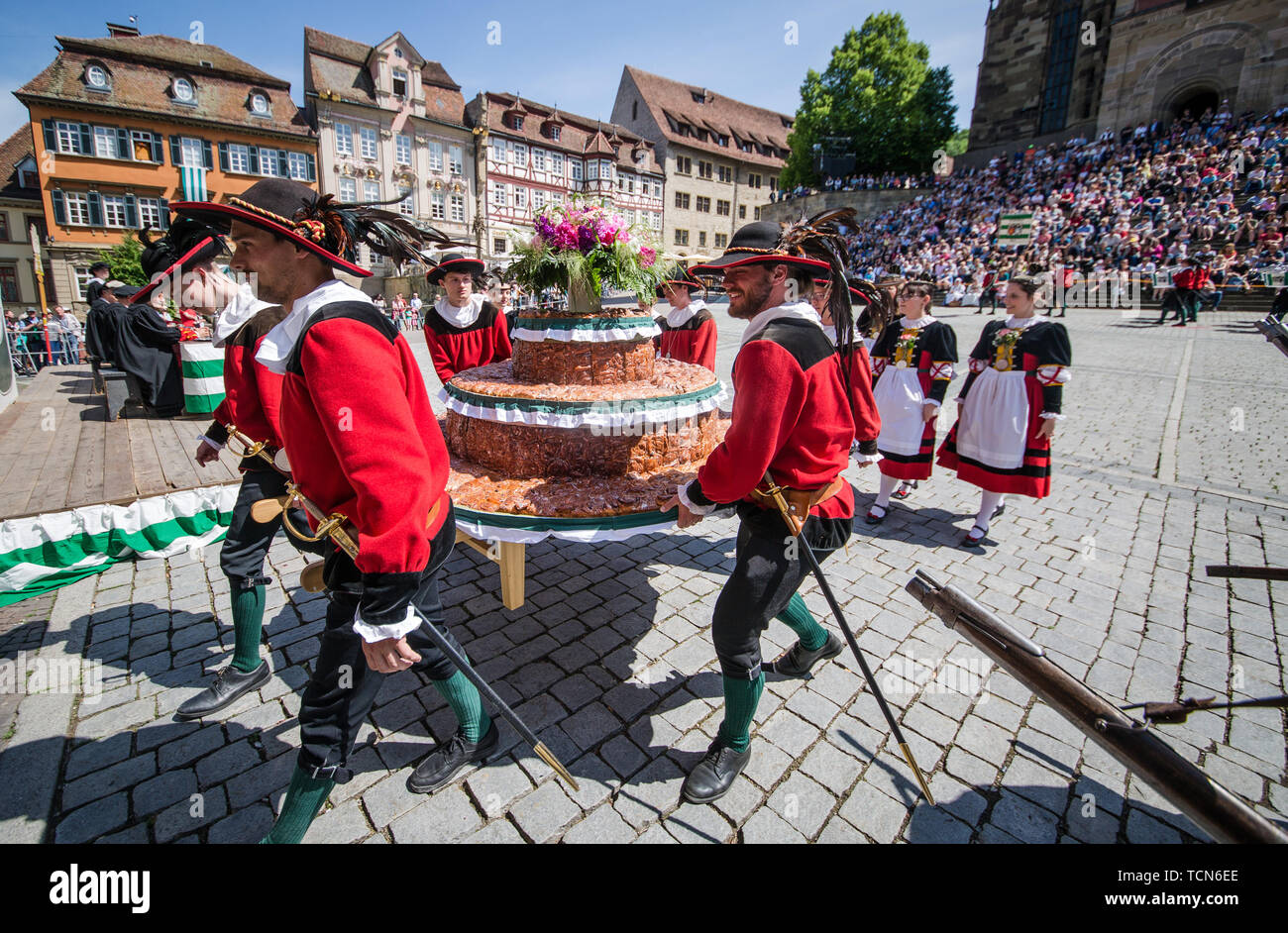 09 June 2019, Baden-Wuerttemberg, Schwäbisch Hall: Members of the association 'Großer Siedershof' carry the gigantic Siederskuchen to the town hall at the cake and fountain festival on the market square. The festival with more than 500 actors and helpers offers a mixture of medieval customs and music. Photo: Christoph Schmidt/dpa - Stock Image