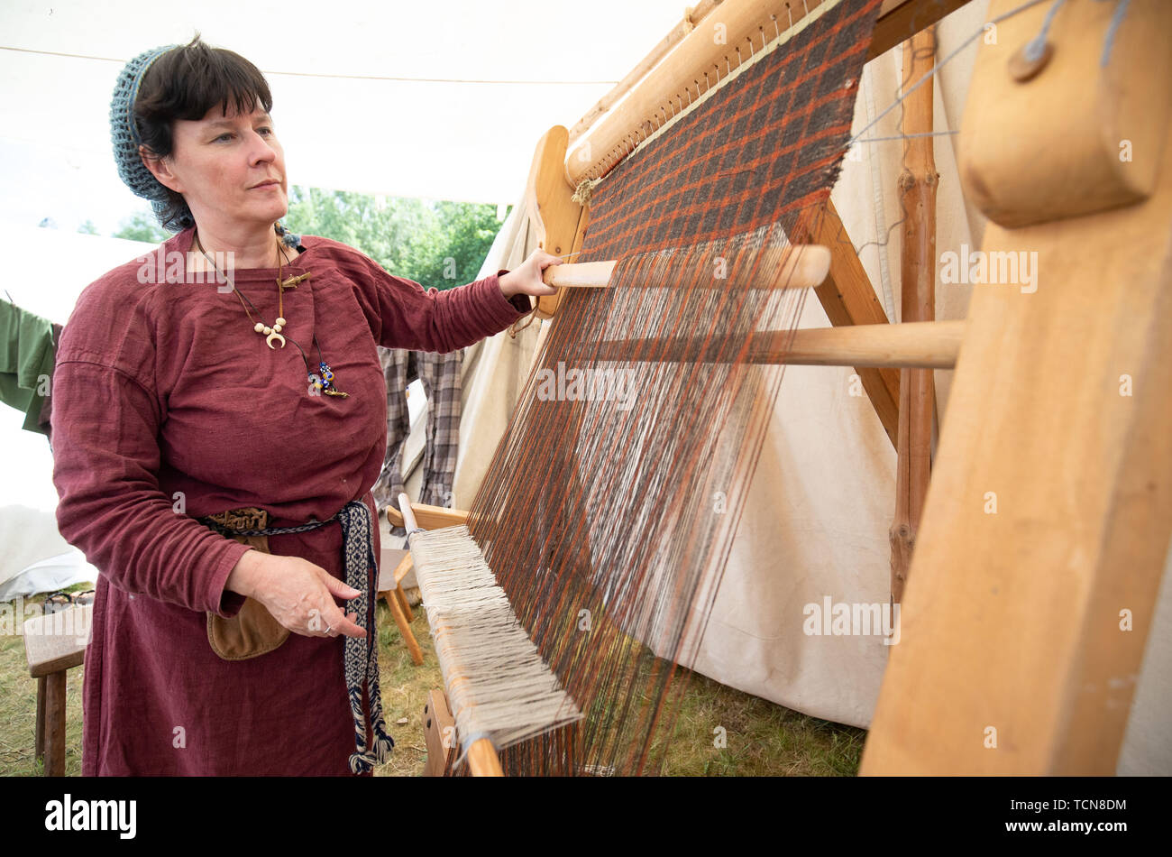 Bramsche, Germany. 09th June, 2019. Germanic actress Andrea Monzel from the group Ars Replika from Wiesbaden weaves on a large weaving frame at the Römer- und Germanentage in the Museum und Park Kalkriese. Hundreds of Roman and Germanic actors take visitors on a journey back in time to 2000 years ago. Credit: Friso Gentsch/dpa/Alamy Live News - Stock Image