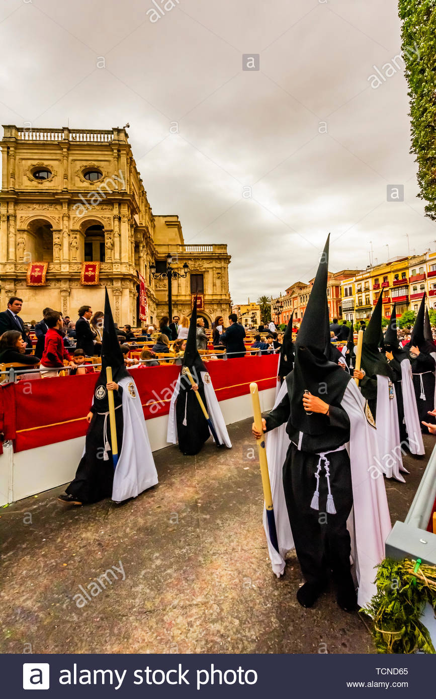 Hooded Penitents (Nazarenos) in the procession of the Brotherhood (Hermandad) La Sed, Holy Week (Semana Santa), Seville, Andalusia, Spain. - Stock Image