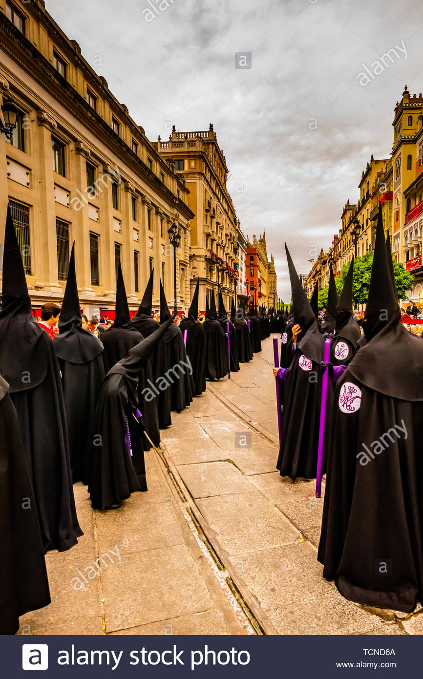 Hooded Penitents (Nazarenos) in the procession of the Brotherhood (Hermandad) San Bernardo, Holy Week (Semana Santa), Seville, Andalusia, Spain. - Stock Image