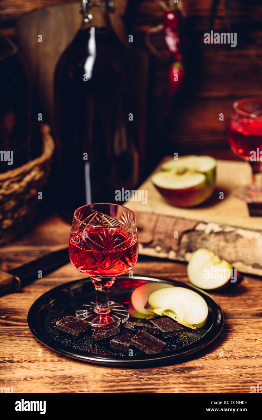 Glass of homemade redcurrant nalivka with apple slices and chocolate on metal plate - Stock Image