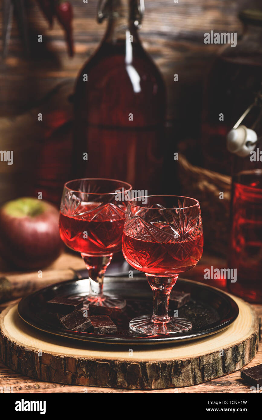 Glass of red liquor with chocolate bars on metal tray - Stock Image