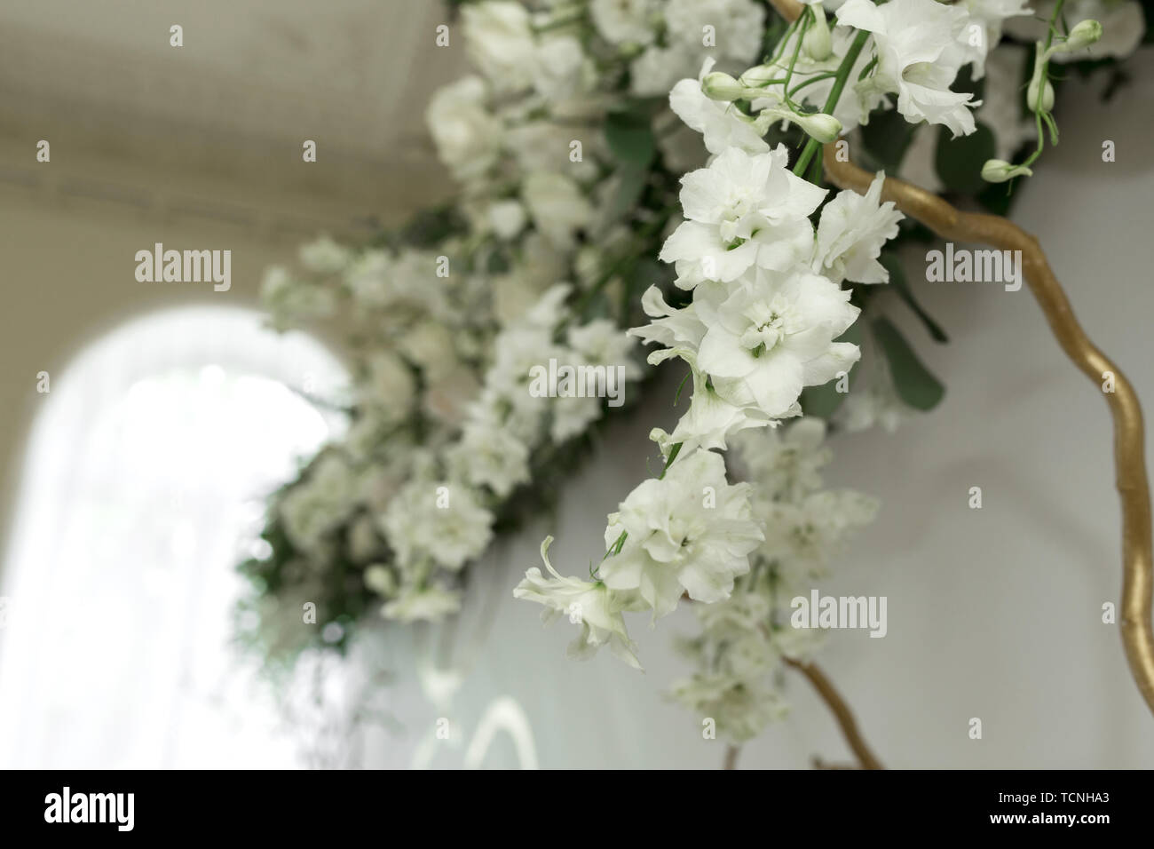 Decoration of the banquet hall, photo zone and wedding arch with eucalyptus leaves, hydrangea and eustoma in the wedding hall. Golden branches. Weddin - Stock Image