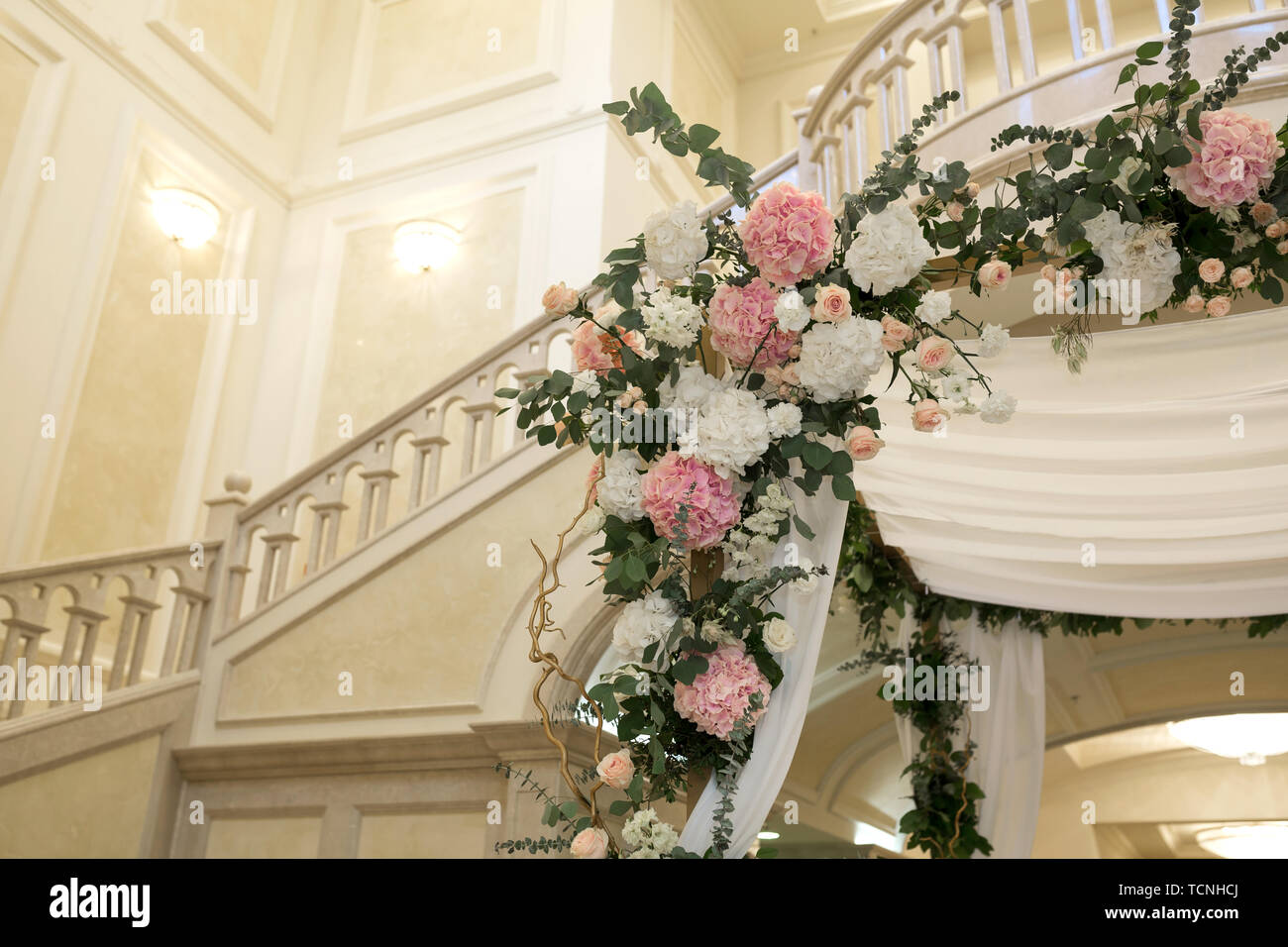 Beautiful wedding huppah decorated with fresh fresh flowers from hydrangea and eucalyptus sheets in a large beautiful wedding hall with a balcony. Wed - Stock Image