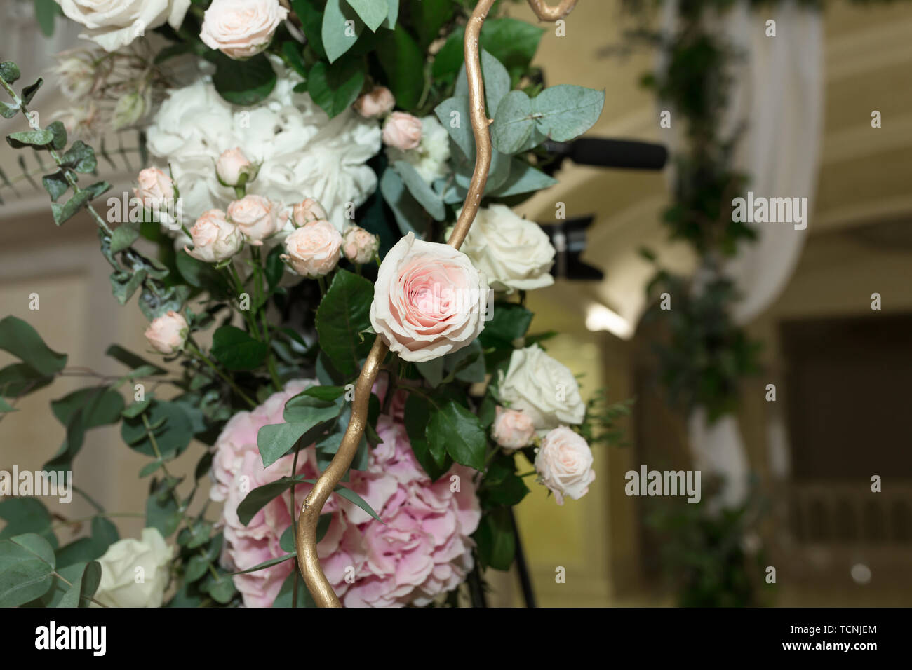 Wedding chuppah decorated with fresh flowers indoor banquet hall of wedding ceremony. Luxury wedding florist decoration artwork. - Stock Image