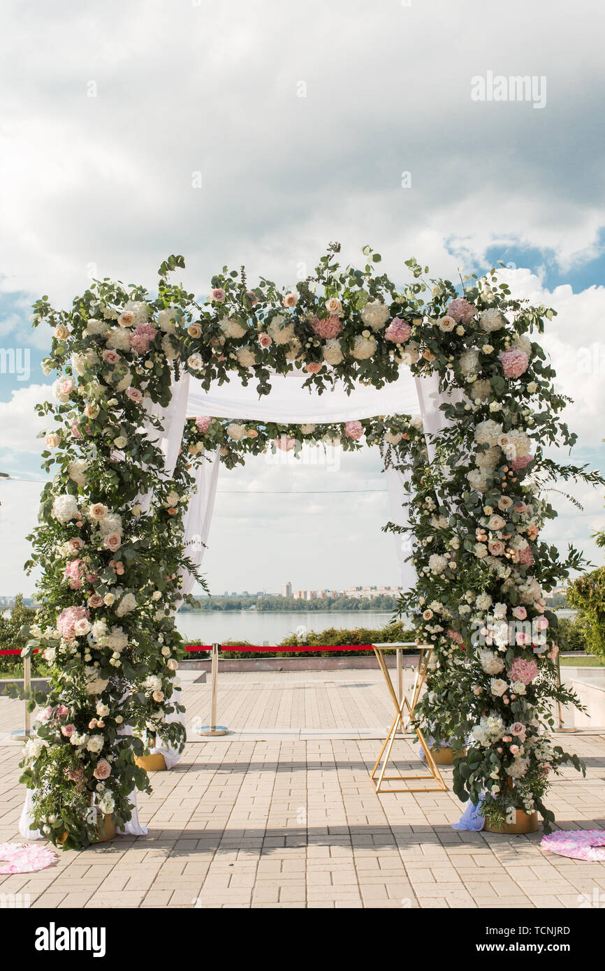 A festive chuppah decorated with fresh beautiful flowers for an outdoor wedding ceremony. - Stock Image
