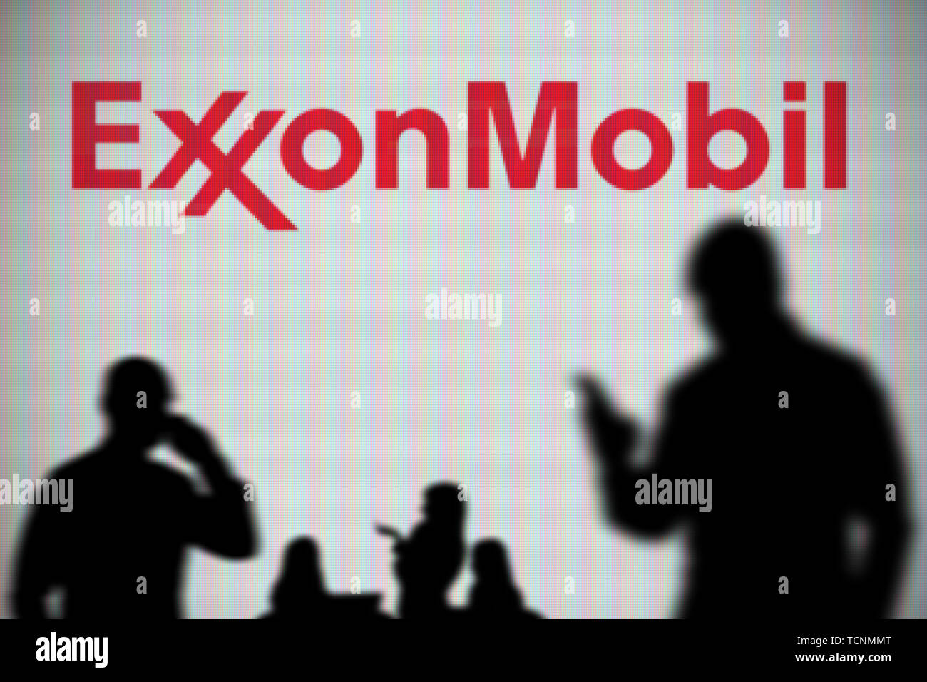 The ExxonMobil logo is seen on an LED screen in the background while a silhouetted person uses a smartphone in the foreground (Editorial use only) - Stock Image