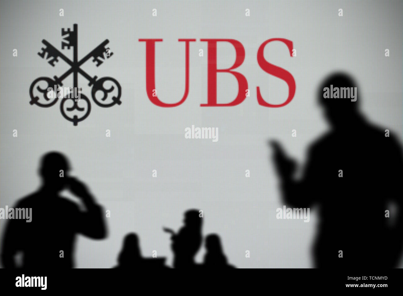 The UBS logo is seen on an LED screen in the background
