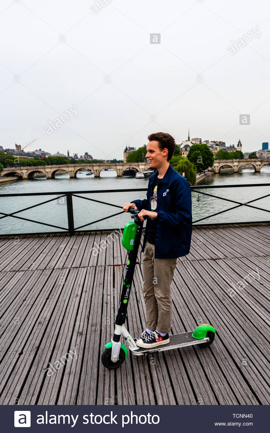 A French teenager rides an electric scooter across the pedestrian Pont des Arts (bridge) , Paris, France. - Stock Image