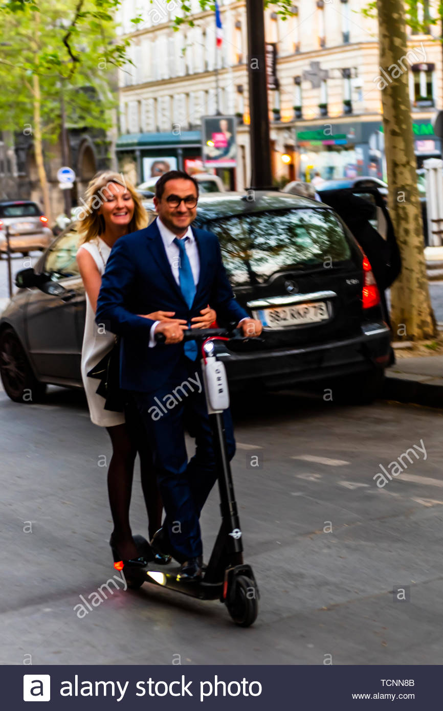 An elegant Parisian couple ride down Avenue Marceau on an electric scooter, Paris, France. - Stock Image