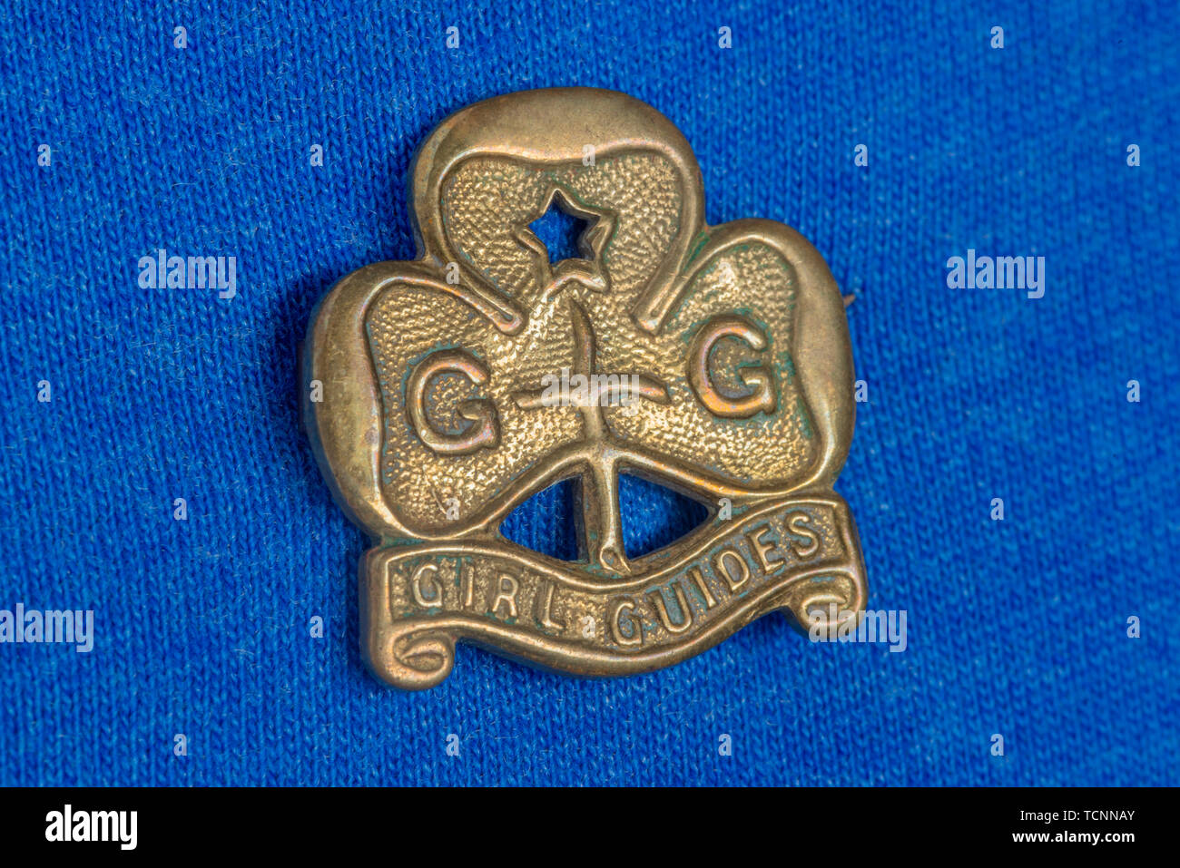 A vintage brass Girl Guides badge shot on a blue cotton background. - Stock Image