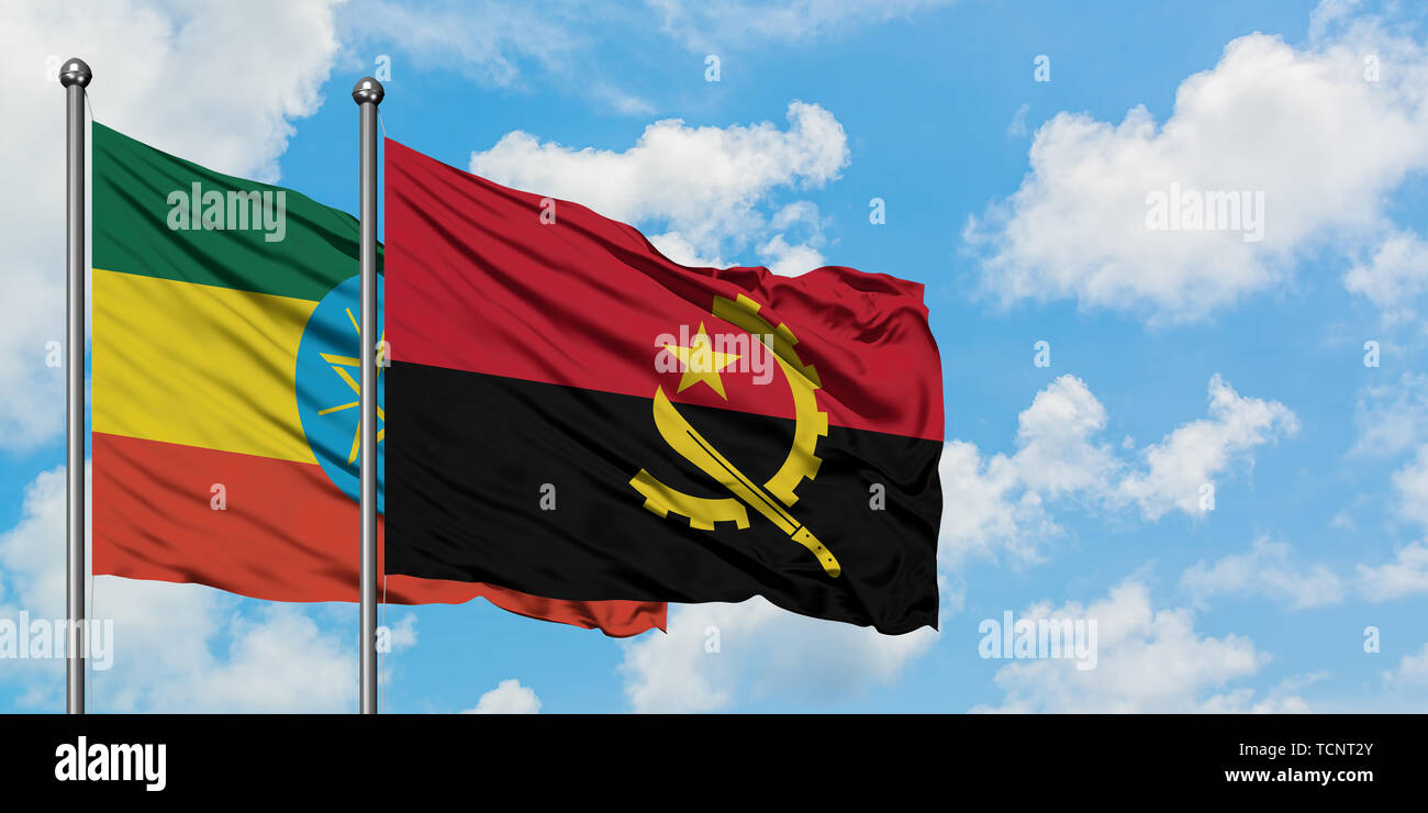 Ethiopia and Angola flag waving in the wind against white cloudy blue sky together. Diplomacy concept, international relations. Stock Photo