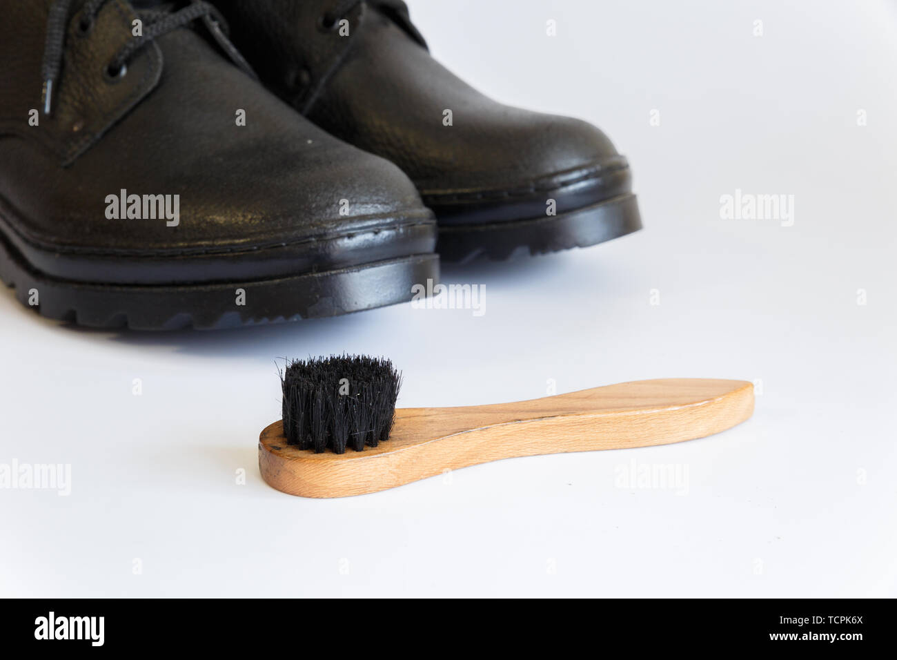 Black shoes and Shoe brush on white background. Shoe care with a brush. Shoe brush. No people. Stock Photo