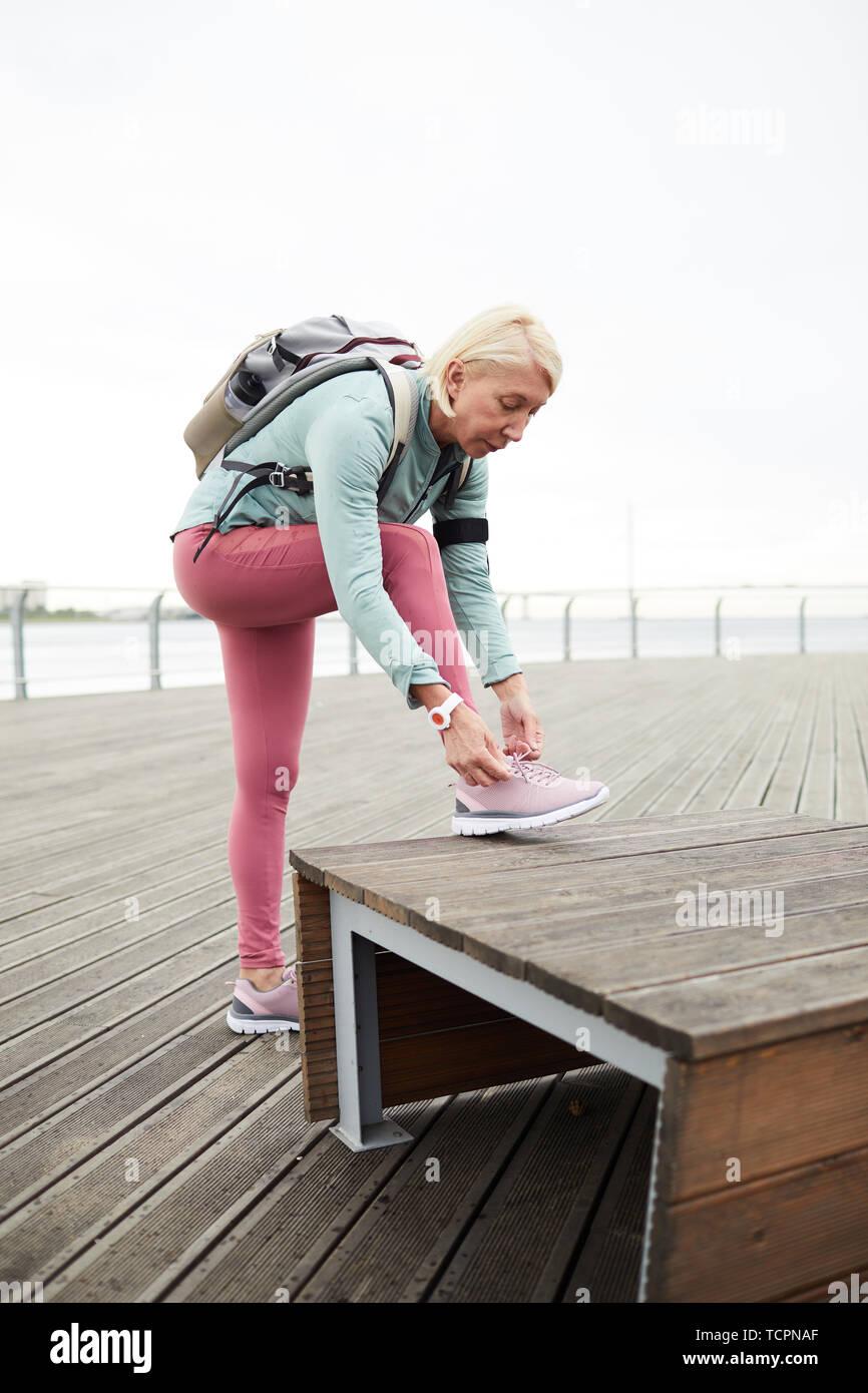 Incredible Blonde Active Female In Sportswear Tying Shoelace On Sports Machost Co Dining Chair Design Ideas Machostcouk